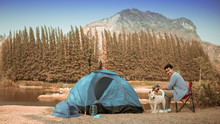 Asian Young Man In Blue Shirt With Cute Puppy Dog Camping On The Lake Hill Mountain View Happy And Enjoy Life