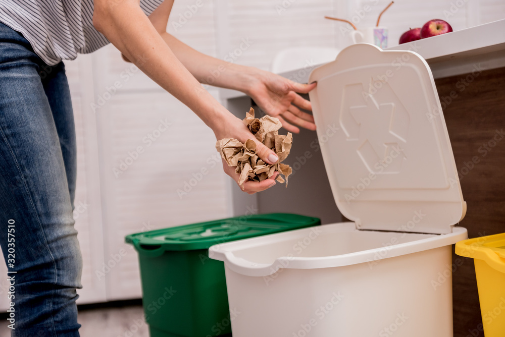 Fototapeta Young girl sorting garbage at the kitchen. Concept of recycling. Zero waste