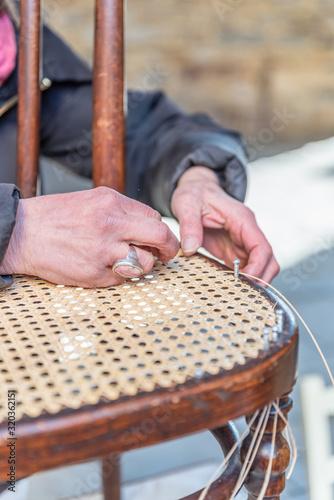The hands of an artisan weave the wooden chair Wallpaper Mural