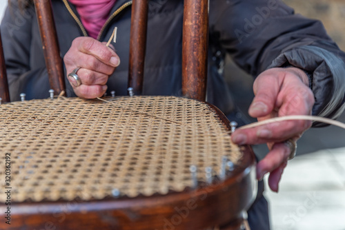 Photo The hands of an artisan weave the wooden chair