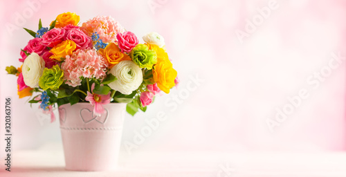 Beautiful spring flowers in vase on white wooden table Canvas Print