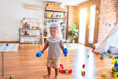 Obraz Beautiful toddler boy playing with plastic basket at kindergarten - fototapety do salonu