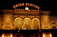 Union Station In Denver, Colorado At Night As The Sign Is Illuminated In Orange And Pierces The Dark Sky.