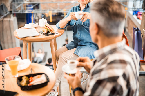 Smiling adult lady holding coffee and looking at interlocutor Canvas Print