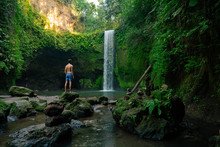 Tourist To Travel In Wild Trip Hiking During Vacation.Travel Hiking. Amazing Tropical Hidden Waterfall Tibumana, Bali, Indonesia. Hidden Paradise Oasis. One Of Famous Waterfall And Landmark In Bali