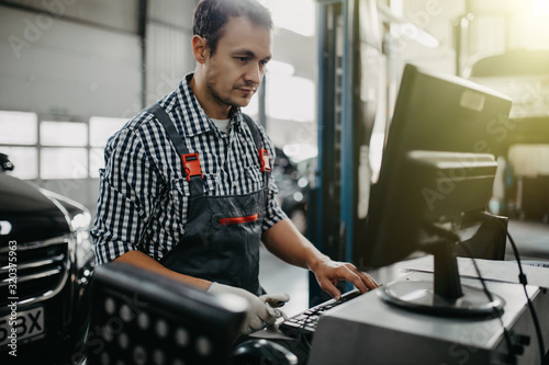 Canvastavla Portrait of happy male mechanic touching computer monitor in auto repair shop