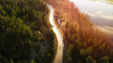 Fototapeta  - Aerial view of winding road through forest with blue lakes in Finland at sunset.