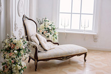 Rococo Style Sofa In A Bright Room Near A Vase Of Flowers And A Large Bright Window With Candlesticks