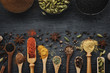 Various aromatic colorful spices and herbs in wooden spoons and scoops. Black ceramic bowls of seasonings. Ingredients for cooking.  Ayurveda treatments. Top view.