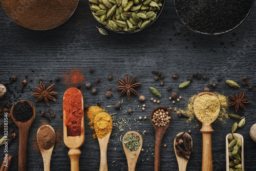 Fototapeta Various aromatic colorful spices and herbs in wooden spoons and scoops. Black ceramic bowls of seasonings. Ingredients for cooking.  Ayurveda treatments. Top view. obraz
