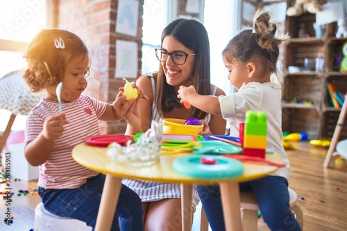 Obraz Young beautiful teacher and toddlers playing meals using plastic food and cutlery toy at kindergarten - fototapety do salonu