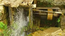 Slow Motion Of A Water Coming Out From Old Mill Stone Wheel