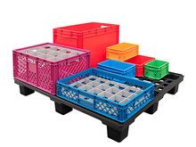 Plastic Multi-colored Crates And Boxes At Transport Pallet Isolated On White Background
