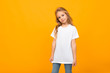 Leinwanddruck Bild - European cute girl in a white T-shirt with a mockup on a yellow background