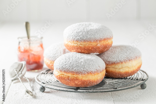 Fotografia, Obraz Closeup of tasty donuts with powdered sugar on white table