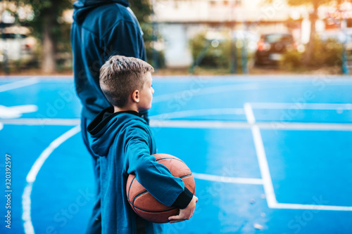 Father and his son enjoying together on basketball court.