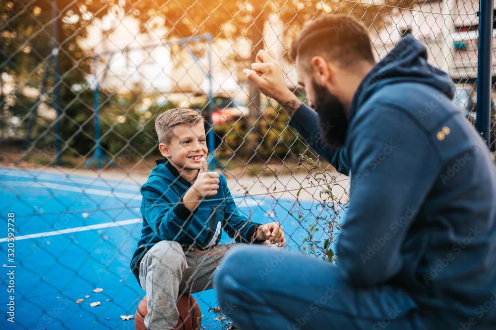 Fototapeta Father and his son enjoying together on basketball court.