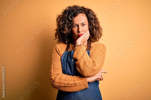Middle age beautiful baker woman wearing apron standing over isolated yellow background thinking looking tired and bored with depression problems with crossed arms Canvas Print