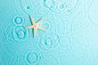 canvas print picture - Water background. Blue water texture, surface of blue swimming pool and starfish. Spa concept background. Flat lay, top view, copy space