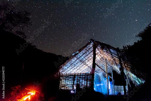 Photo Noche estrellada desde una cabaña y una pequeña hoguera