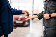 Worker Receiving A Car Key Fob From A Businessman
