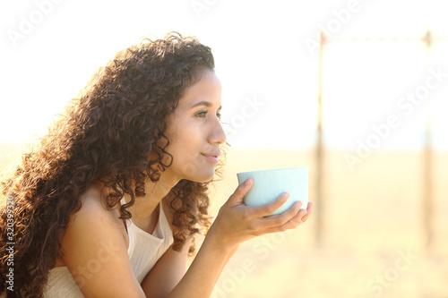 Pensive latin woman holding coffee mug looks away Wallpaper Mural