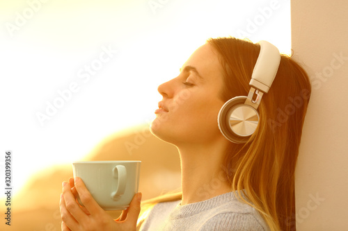 Fototapeta Relaxed woman listening to music with headphones obraz