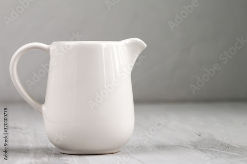 Fototapeta Milk in white ceramic jug isolated on grey background, top view and empty space for text obraz