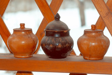 A Row Of Clay Pots With Lids O...