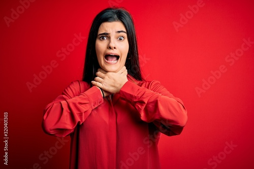 Photo Young beautiful brunette woman wearing casual shirt standing over red background shouting and suffocate because painful strangle