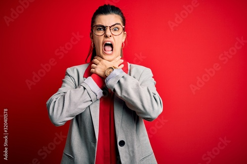 Young beautiful brunette businesswoman wearing jacket and glasses over red background shouting suffocate because painful strangle Canvas Print