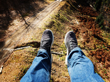 A Pair Of Male Legs In Jeans And Sneakers View From A Chair Lift On A Trail In A Mountain Valley