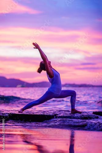 Fototapeta Woman practices yoga at seashore