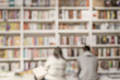 Leinwanddruck Bild - Abstract blurred unrecognizable woman and man in bookstore, bookshelves with books, soft focus. Concept of learning, school, culture, education