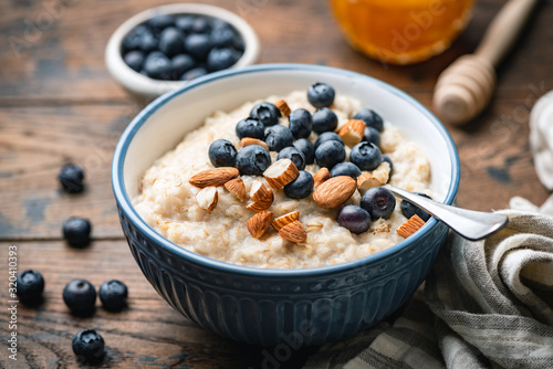 Obraz Oatmeal porridge with blueberries, almonds in bowl on wooden table background. Healthy breakfast food - fototapety do salonu