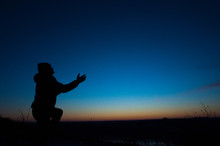 Silhouetted Men On A Background Of Blue Sky And Sunset. Kneeling Prayer To God. Glorification.