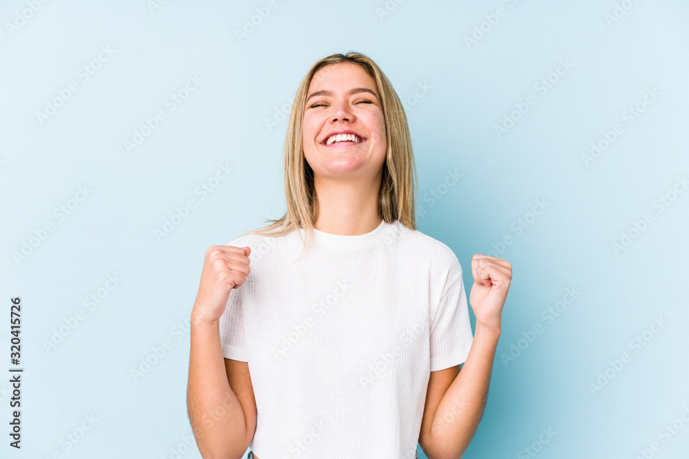 Fototapeta Young blonde caucasian woman isolated celebrating a victory, passion and enthusiasm, happy expression.