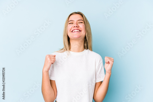 Fototapeta Young blonde caucasian woman isolated celebrating a victory, passion and enthusiasm, happy expression