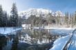 Leinwanddruck Bild Idyllic winter wonderland with mountain lake in the Alps