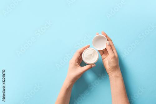 Fototapeta Female hands with jar of cream on color background obraz