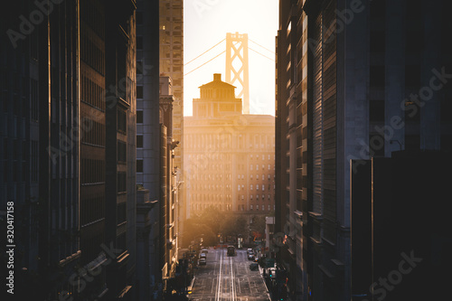 fototapeta na ścianę Downtown San Francisco with famous California Street illuminated in first golden morning light at sunrise in summer, San Francisco, California, USA