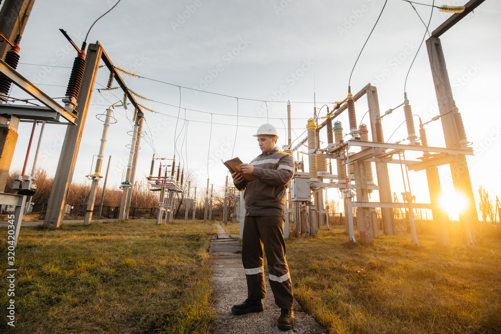 Fototapeta The energy engineer inspects the equipment of the substation. Power engineering. Industry