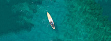 Aerial Drone Ultra Wide Top Down Photo Of Male Stand Up Paddle Board Surfer Paddling In Tropical Exotic Sea With Turquoise Calm Water