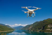 Uav Drone With Digital Camera Over Lake In Mountains