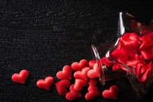 Red Hearts From Glass Bottle On Black Background. Love And Valentine's Day Concept.