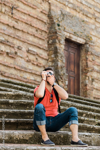 Fototapety, obrazy: Young male traveler sitting on steps of an old town in Tuscany taking a photo on a vintage camera
