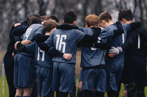 Fotografía Soccer team with junior coach gathering together in a circle, to strategize and motivate