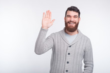 Cheeerful Young Bearded Man Is Saying Hi Making Hello Gesture, And Smiling At The Camera.