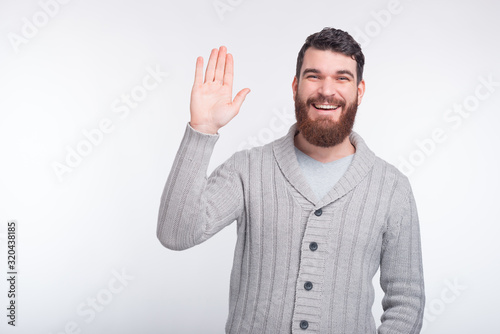 Cheeerful young bearded man is saying hi making hello gesture, and smiling at the camera Poster Mural XXL