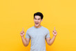 Happy smiling young Asian man with hands poiting up